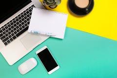 Conception ?tendue plate de bureau de travail avec le carnet, le smartphone et le cactus de labtop sur le fond vert et jaune photos stock
