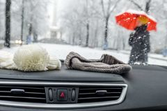 Conceptional winter shot of beanies in a car behind the front window while lady with red umbrella walks by.  Royalty Free Stock Photos