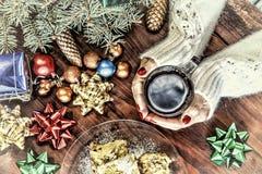 Concepto: Año Nuevo, la Navidad en una ambiente familiar acogedora Una mujer en un suéter del blanco sostiene una taza de té, al  Foto de archivo libre de regalías