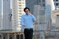 Concepto acertado del asunto Exposición doble del hombre de negocios asiático joven feliz que camina y que lanza su corbata en c  imagenes de archivo