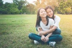 Concepto adorable y de familia: La sentada de la mujer y del niño se relaja en hierba verde Ellos que abrazan y felicidad sonrien imagen de archivo