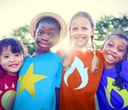 Concepto alegre del verano de la amistad de los niños del super héroe Foto de archivo
