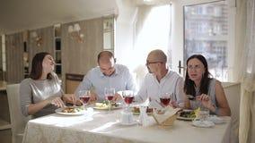 Concepto - amigos felices que comen y que beben en el restaurante Cuatro amigos en el restaurante, comen la carne y beber el vino almacen de video