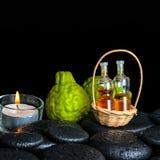 Concepto aromático del balneario de frutas de la bergamota, de vela y de esse de las botellas Foto de archivo