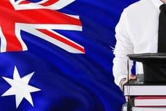 Concepto australiano acertado de la educación del estudiante Sostener los libros y el casquillo de la graduación sobre fondo de l fotos de archivo