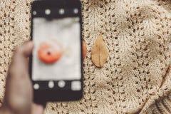 Concepto blogging de Instagram mano que sostiene el teléfono y que toma la foto Imágenes de archivo libres de regalías