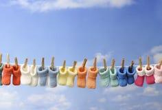 Concepto: botines coloridos del bebé en una línea de ropa Foto de archivo libre de regalías