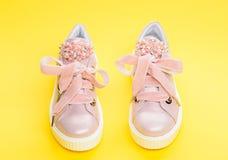 Concepto cómodo del calzado Zapatos lindos en fondo amarillo Pares de pálido - zapatillas de deporte femeninas rosadas con las ci Imagen de archivo libre de regalías