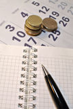 Concepto calculador de los costos Pluma, calendario, cuaderno, y monedas foto de archivo