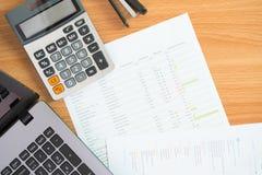 Concepto, calculadora y documentos de la gestión financiera del presupuesto personal con un ordenador portátil en la tabla foto de archivo