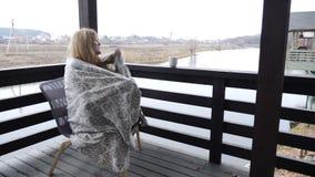 Concepto casero acogedor La mujer joven se sienta en terraza de la casa abierta en tela escocesa que goza del café caliente 4 K metrajes