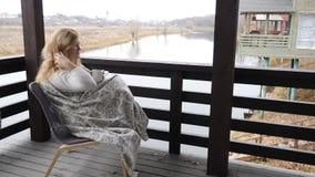 Concepto casero acogedor La mujer joven se sienta en terraza de la casa abierta en tela escocesa que goza del tiempo y del café c almacen de metraje de vídeo