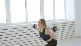 Concepto casero de la aptitud La mujer joven con un barbell hace ejercicios en un interior blanco almacen de video