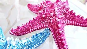 Concepto casero de la decoraci?n primer, dos estrellas de mar azules y rosadas en una tabla de cristal transparente almacen de metraje de vídeo