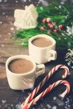 Concepto casero de la Navidad con dos bebidas, piruletas y juguetes calientes ho Fotografía de archivo libre de regalías