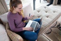 Concepto casero de las compras del web con la mujer hermosa joven sonriente Imágenes de archivo libres de regalías