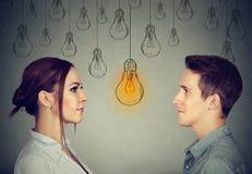 Concepto cognoscitivo de la capacidad de las habilidades, varón contra hembra Hombre y mujer que miran la bombilla brillante fotos de archivo libres de regalías