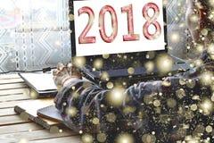 Concepto: Comienzo del Año Nuevo En la pantalla 2018 Un freelancer utiliza un ordenador portátil en casa Imagen de archivo