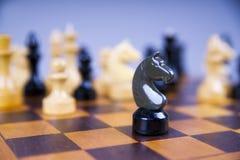 Concepto con los pedazos de ajedrez en un tablero de ajedrez de madera Foto de archivo