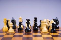 Concepto con los pedazos de ajedrez en un tablero de ajedrez de madera Fotografía de archivo