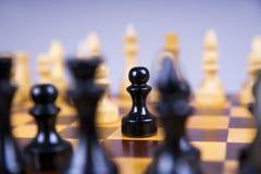 Concepto con los pedazos de ajedrez en un tablero de ajedrez de madera Imagenes de archivo