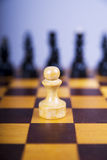Concepto con los pedazos de ajedrez en un tablero de ajedrez de madera Foto de archivo libre de regalías