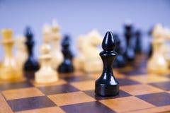 Concepto con los pedazos de ajedrez en un tablero de ajedrez de madera Imagen de archivo libre de regalías