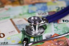 Concepto costado médico - estetoscopio en billetes de banco euro de los billetes fotos de archivo libres de regalías
