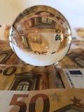 Concepto creativo, bola de cristal y billetes de banco de las finanzas fotografía de archivo libre de regalías