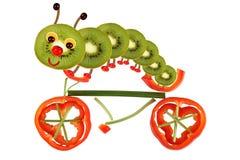 Concepto creativo de la comida Pequeña oruga divertida en una bicicleta mA Imagen de archivo
