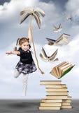 Concepto creativo de la educación, mosca de la muchacha del niño en el libro imagen de archivo libre de regalías