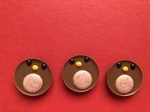 Concepto creativo de la Navidad, petirrojos del chocolate en rojo fotos de archivo