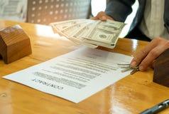 Concepto, dólares y casas de compra caseros del modelo con el papel del contrato imágenes de archivo libres de regalías