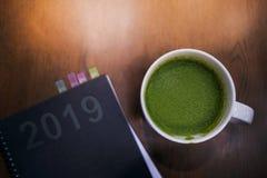 Concepto de 2019 años Gestión de tarea o cepillado para el nuevo desafío del negocio, la taza de té verde caliente y el cuaderno  imagen de archivo