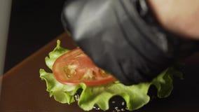 Concepto de acabamiento que cocina una hamburguesa negra de la hamburguesa con los bollos negros Verduras y carne cortadas Pruebe almacen de video