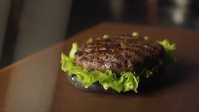 Concepto de acabamiento que cocina una hamburguesa negra de la hamburguesa con los bollos negros Verduras y carne cortadas Pruebe almacen de metraje de vídeo