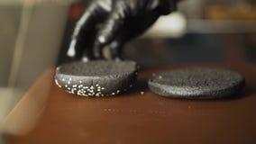 Concepto de acabamiento que cocina una hamburguesa negra de la hamburguesa con los bollos negros Verduras y carne cortadas Pruebe metrajes