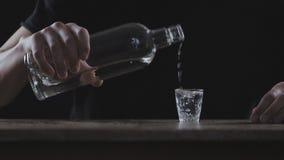 Concepto de alcoholismo El hombre vierte el alcohol en un vidrio y bebe en un cuarto oscuro en la cámara lenta almacen de video