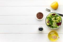 Concepto de alimento sano Ensalada fresca en cuenco con la semilla de lino en la tabla de madera blanca Foto de archivo