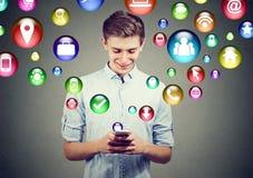 Concepto de alta tecnología de la tecnología móvil Hombre joven feliz que usa el teléfono elegante con los medios iconos sociales Imagenes de archivo