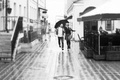 Concepto de amor: pares cariñosos debajo de un paraguas que camina abajo de la calle de la ciudad foto blanco y negro en retro Imagen de archivo