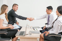 Concepto de apretón de manos acertado de hombres de negocios en oficina fotografía de archivo libre de regalías