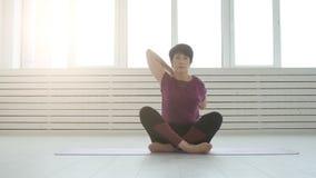Concepto de armonía, de deporte y de salud Mujer de mediana edad que hace yoga en un interior blanco metrajes