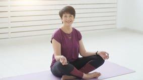 Concepto de armonía, de deporte y de salud Mujer de mediana edad que hace yoga en un interior blanco almacen de metraje de vídeo