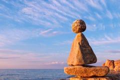 Concepto de armonía y de balanza Zen de la roca en la puesta del sol Foto de archivo libre de regalías