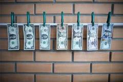 Concepto de blanqueo de dinero - los dólares se están secando en el listón encendido en fondo de la pared de ladrillo Imagenes de archivo