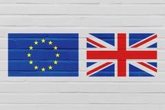Concepto de Brexit con la bandera de la unión europea y de Reino Unido en la pared de ladrillo fotografía de archivo