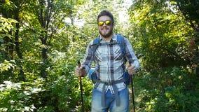 Concepto de caminar y de turismo Un hombre está caminando a lo largo de un bosque del verano metrajes