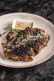 Concepto de cocina americana Filete frito, jugoso del cerdo en pimienta negra con tomillo y salsa de queso blanca en un plato de  foto de archivo libre de regalías