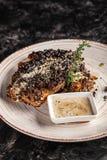 Concepto de cocina americana Filete frito, jugoso del cerdo en pimienta negra con tomillo y salsa de queso blanca en un plato de  fotos de archivo